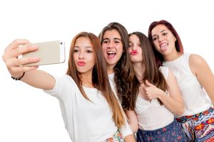 Group portrait of cute teen girlfriends taking self portrait.Isolated on white background.